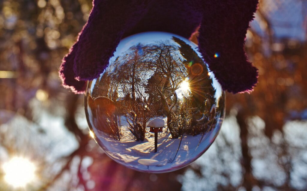 Photograph of a person holding a circular reflecting ball resembling a snow-globe