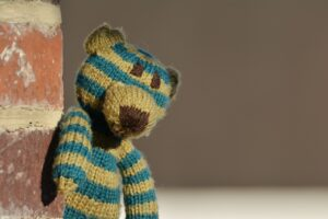 Photograph of a worn out green and yellow stripped teddy bear looking sad