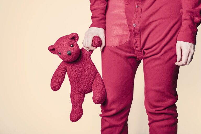 Photograph of a child in red pajamas holding a red teddy bear