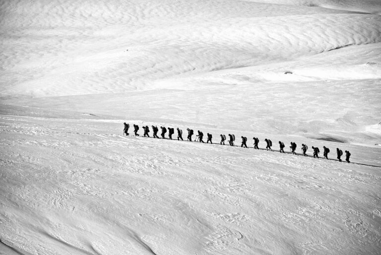 Photo of a line of people hiking through the snow.
