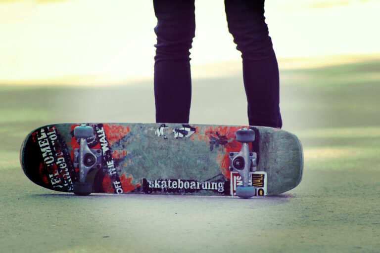 Photograph of a skateboard on its side with the legs of a person standing behind it