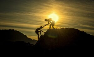 Photograph of sunset with one person helping another up a hill