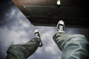 Photograph of a persons legs hanging over a building